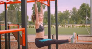Closeup portrait of young pretty sporty fitness girl making exercises on the athletic field in urban city outdoors.  stock footage