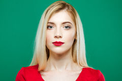 Closeup Portrait of Young Pretty Woman with Sensual Lips and Professional Makeup Wearing Red Top on Green Background in Royalty Free Stock Photography
