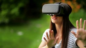 Closeup Portrait of Young Pretty Woman Wearing Striped Shirt is Using Virtual Reality Glasses Sitting Near the Lake in. The City Park, HD stock footage