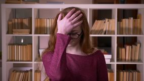 Closeup portrait of young redhead attractive caucasian female student in glasses making a face palm being annoyed and. Tired looking at camera in the college stock video