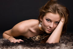 Closeup portrait of young savage woman on fur Royalty Free Stock Images