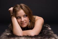 Closeup portrait of young savage woman on fur Stock Photos