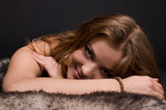 Closeup portrait of young savage woman on fur Royalty Free Stock Photo