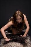 Closeup portrait of young savage woman on fur. Closeup portrait of young emotional savage woman on animal fur Stock Photo