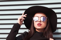 Closeup portrait of young seductive model wears hat and sunglasses. Woman posing at the background of shutters in sunny day royalty free stock image