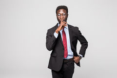 Closeup portrait young serious african businessman placing finger on lips saying, shhh, be quiet, silence, isolated grey backgroun. Closeup portrait young Stock Photo