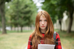Closeup portrait of young serious cute redhead student woman in red plaid jacket holding her papers posing outdoors with blurred p Stock Photography