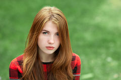 Closeup portrait of young serious redhead woman in red plaid jacket looking into camera with blurred green grass background Royalty Free Stock Photography