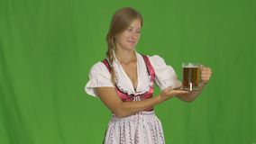 Young sexy Oktoberfest waitress, wearing a traditional Bavarian dress, serving big beer mug on green isolated background stock video footage