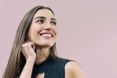 Closeup portrait of young smiling woman, caucasian female`s face on beige pink pastel background royalty free stock images