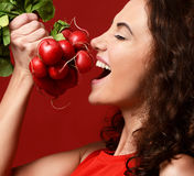 Closeup portrait of young sport woman eating fresh radish green. Leaves. Diet. Healthy eating concept on red background Stock Photo