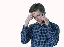Closeup portrait of young stressed business man, corporate employee, student talking on cell phone. Royalty Free Stock Photos