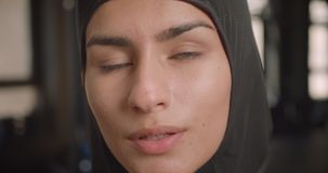 Closeup portrait of young successful athletic muslim female looking at camera with determination standing in gym indoors.  stock video