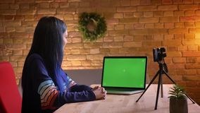 Closeup portrait of young trendy caucasian female video blogger live streaming on the camera with a laptop with green stock video