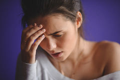 Closeup portrait young upset sad woman thinking deeply about something with headache holding her hands Stock Photo