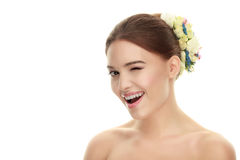 Closeup portrait of young winking adorable brown-haired woman with makeup and flower headpiece Stock Image