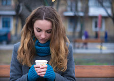Closeup portrait of young woman drinking coffee in the park. Royalty Free Stock Photography