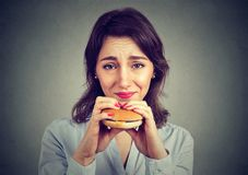 Woman with guilty feeling to eat a hamburger stock image