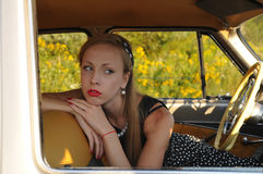 Closeup portrait of young woman inside old-fashioned car Royalty Free Stock Image