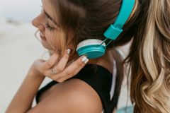Closeup portrait young woman with long curly hair enjoying lovely music through blue headphones. Walking on seafront royalty free stock images