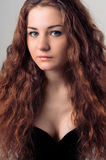 Closeup portrait of young woman with long red hairs looking at c Royalty Free Stock Photos