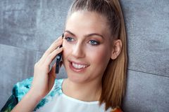 Closeup portrait of young woman with mobile. Closeup portrait of young blonde woman talking on mobilephone, smiling, looking away Stock Images