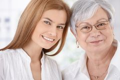 Closeup portrait of young woman and mother smiling. Closeup portrait of young attractive women and senior mother, both smiling, looking at camera Stock Photo