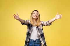 Closeup portrait, young woman motioning with arms to come and give her a bear hug, isolated on yellow background. Closeup portrait, young woman motioning with stock photos