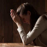 Closeup portrait of a young woman praying. Indoors Stock Photography
