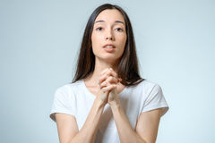 Closeup portrait of a young woman praying. On white background royalty free stock photo