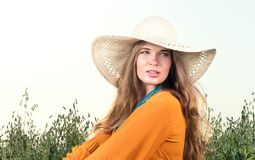 Closeup portrait of young woman sitting in a field. Straw hat and red dress. Summer look Royalty Free Stock Image