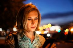 Closeup portrait of a young woman using a smartphone outdoor royalty free stock image