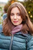 Closeup portrait of a young woman in the winter down jacket royalty free stock photography