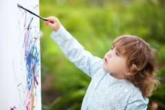 Closeup portret of a little talented painter, toddler girl. Cute toddler girl painting on the easel in the garden and having fun. Closeup portrait. Talented Stock Images