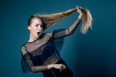 Closeup portret of young beautiful woman in amazement trying to raise his hair on blue grey background. emotions. Model test Royalty Free Stock Images