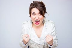 Closeup pose of an angry woman screaming in the white elegant jacket.  Royalty Free Stock Photos