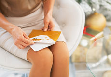 Closeup on postcard in hand of woman sitting near christmas tree Royalty Free Stock Photo