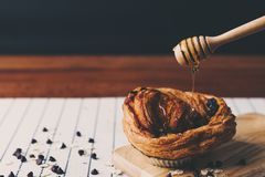 Closeup pouring honey to chocolate croissant. Eating and traditional breakfast concept royalty free stock photos