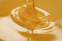 Closeup of pouring organic honey. Amber golden color Royalty Free Stock Photo