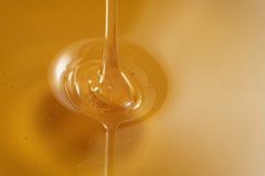 Closeup of pouring organic honey. Amber golden color Royalty Free Stock Photos