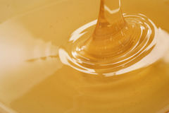 Closeup of pouring organic honey. Amber golden color Royalty Free Stock Image