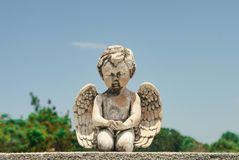 Closeup of praying baby angel statue on tombstone with trees and blue sky behind stock photo