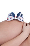 Closeup of a pregnant woman with blue baby shoes Stock Image