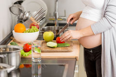 Closeup of pregnant woman cutting vegetables on wooden board Royalty Free Stock Photo