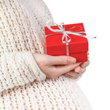 Closeup of pregnant woman holding gift box. Closeup of pregnant woman wearing knitted sweater holding red gift box isolated on white background stock photography