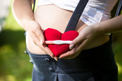 Closeup of pregnant woman holding positive pregnancy test on hea Stock Image