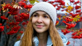 Blonde long haired girl in hat jacket smiles by rowan trees stock video