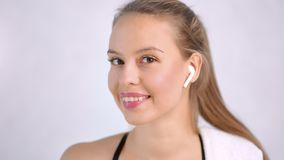 Closeup pretty fit lady with beauty skin wearing headphones isolated at light studio background