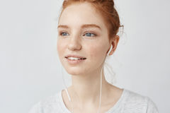 Closeup of pretty ginger girl listening to streaming music with wired earphones. Royalty Free Stock Photos