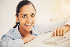 Closeup pretty Indian businesswoman smiling at desk in modern of Stock Image